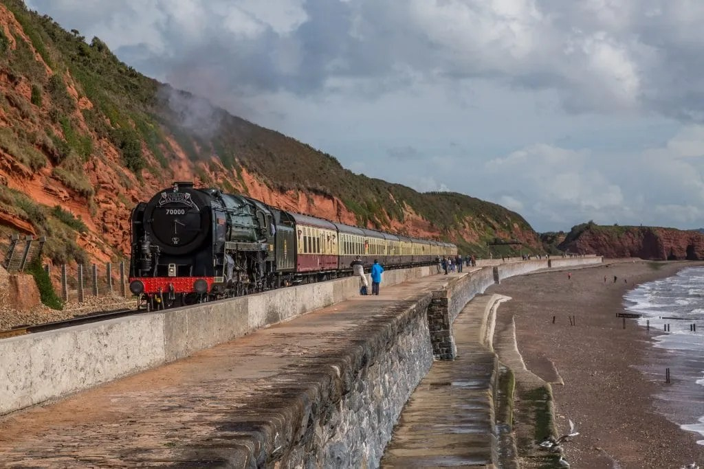 Steam locomotive train BR Standard Class 7MT4-6-2 No: 70000 'Britannia' is seen passing Dawlish