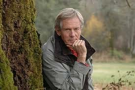 Robert Bateman poses beside moss covered tree