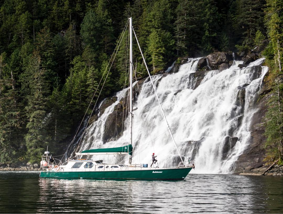 The Achiever rests in front of a waterfall.