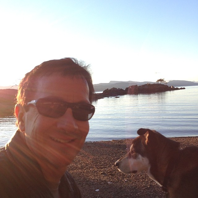 On the beach, Raincoast Conservation Executive Director Chris Genovali stares smiling at the camera while a brown dog Atticus holds a stick in his mouth beside him