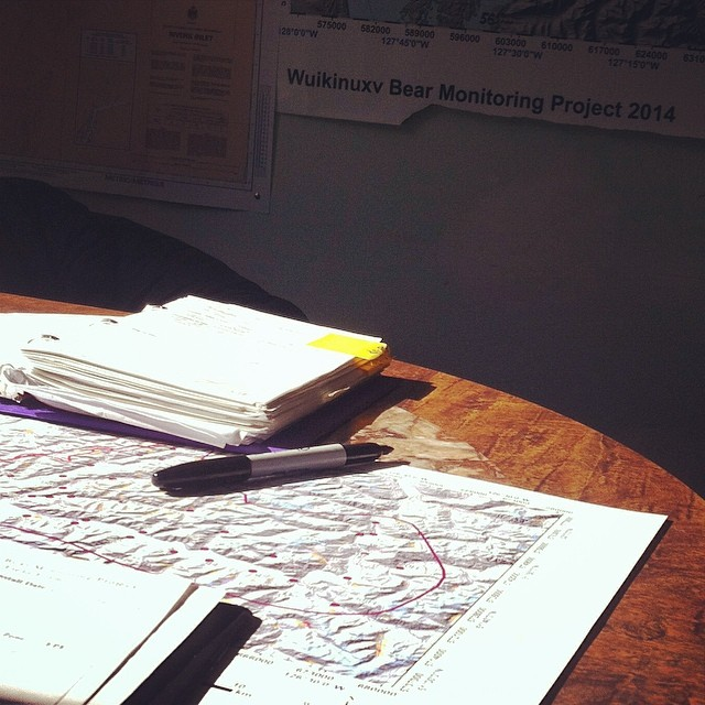 Notebook, pen and map on a table illustrating Raincoast scientists planning out helicopter sampling of Grizzlies in Wuikinuxv