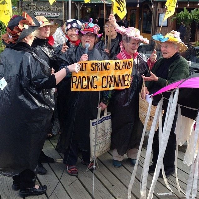 A group of older women holding a sign that reads Raging Grannies protest against Kinder Morgan and in support of saving the Salish Sea besides the Raincoast table at Salt Spring island