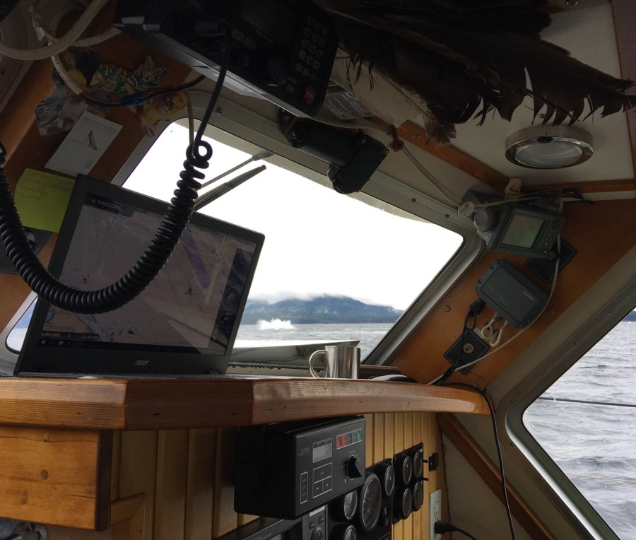 Looking out the window from the wood panelled cabin of a sailboat to see a large splash as a whale leaps out of the water.