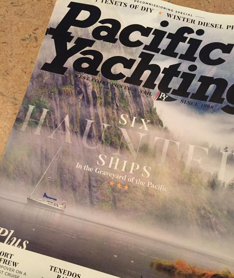 A Pacific Yachting magazine with a cover photo of mist rising on the ocean and a green sailboat (Achiever) in the distance.