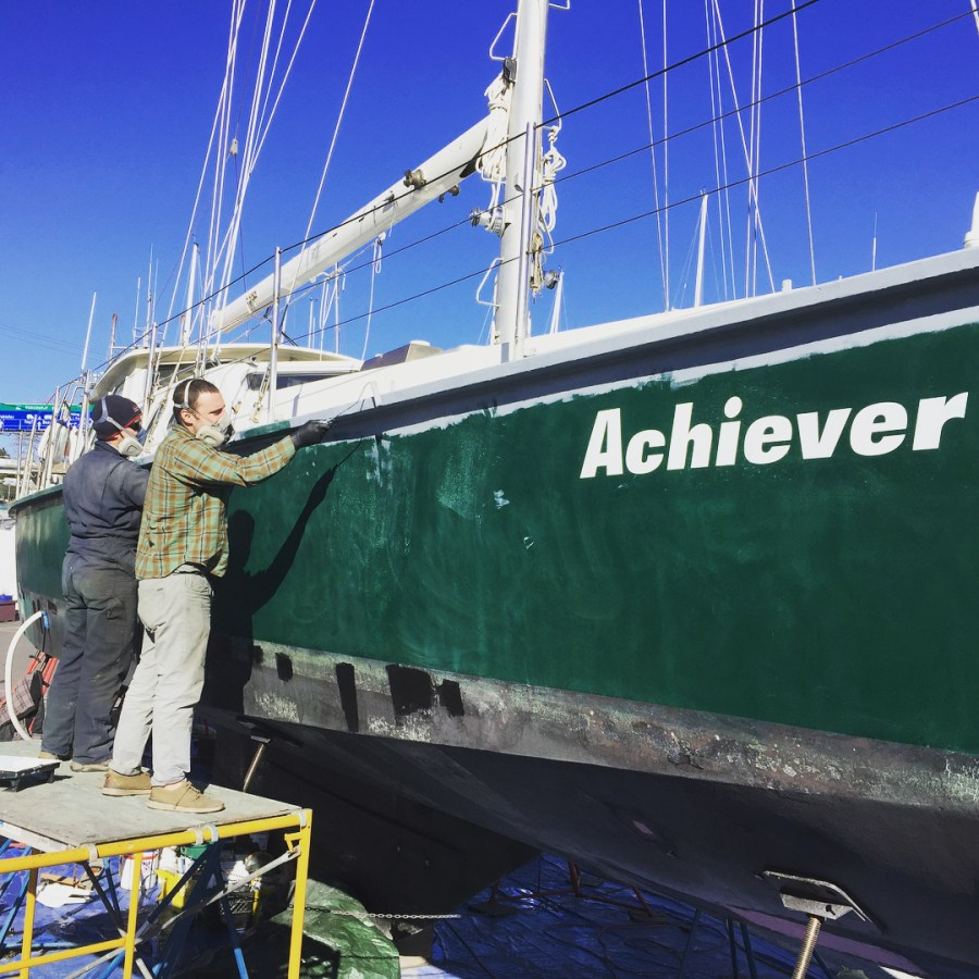 "A green boat lifted over a blue tarp with white writing on the side saying ""Achiever."" A masculine person stands on a ladder beside the boat painting."