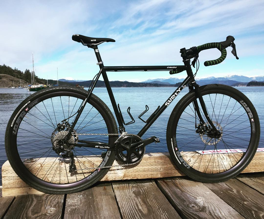 A bike on a dock with the ocean behind it. The sky is bright blue.