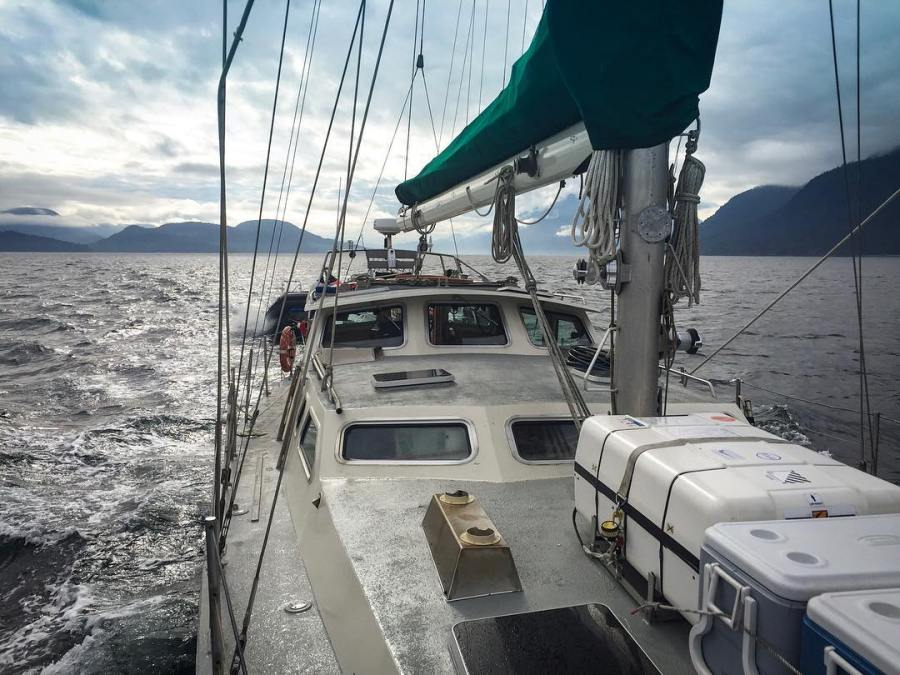 Onboard a sailboat with a white deck looking out on a grey ocean and a bright but cloudy sky.