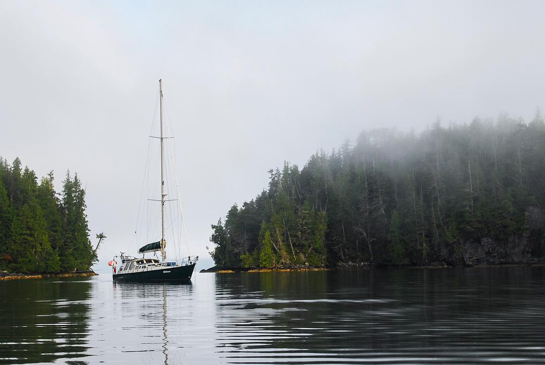 A sailboat (the Achiever) on the water between two tree covered tips of land. It is misty and the sky is grey.
