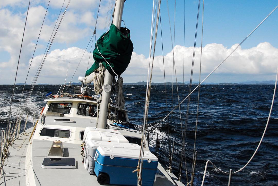 Photo taken from back of sailboat with a white deck and green hull sailing on the ocean with a blue sky and white fluffy clouds.
