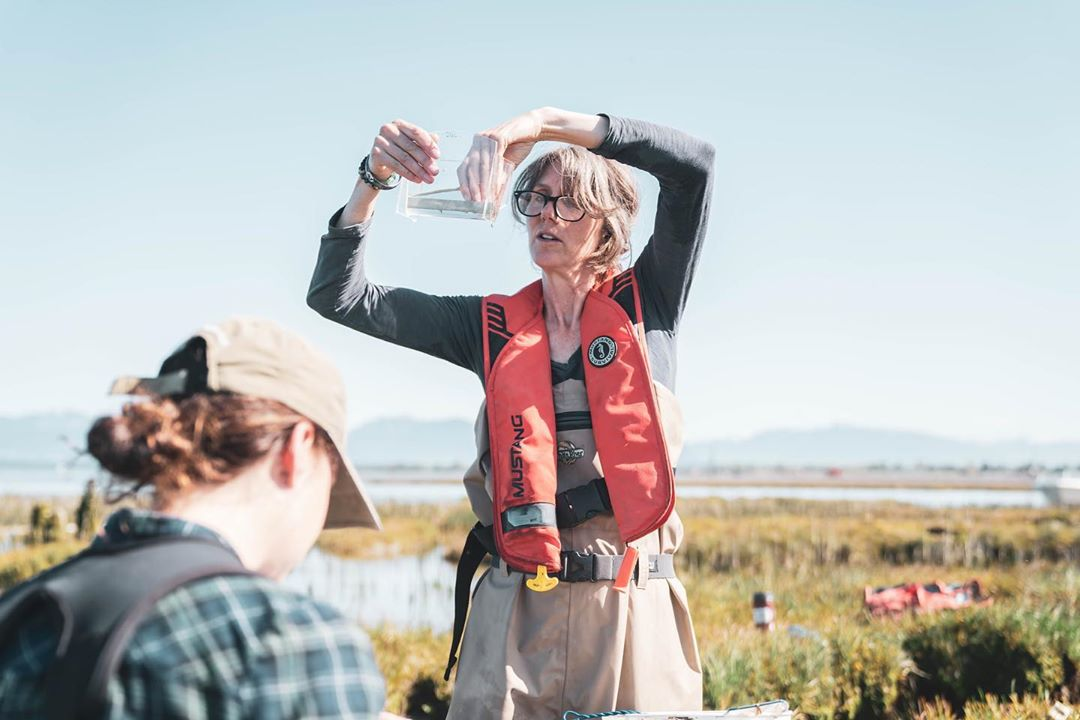 Misty in a red life jacket and glasses holding up a clear container holding small fish. Marshy estuary land is behind her,