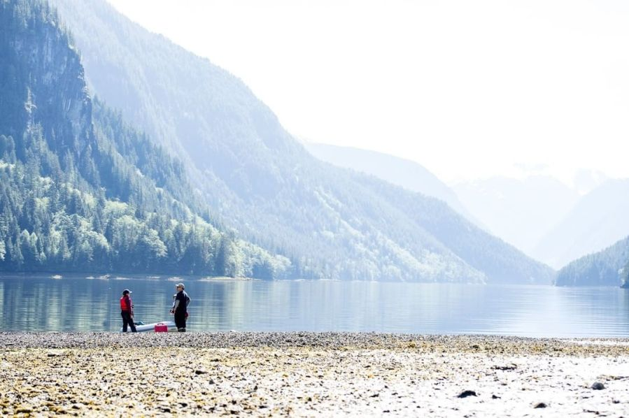Two people in the middle left stand on a rocky beach looking out at a large expanse of water with tree covered mountains rising in front of them also to the left.