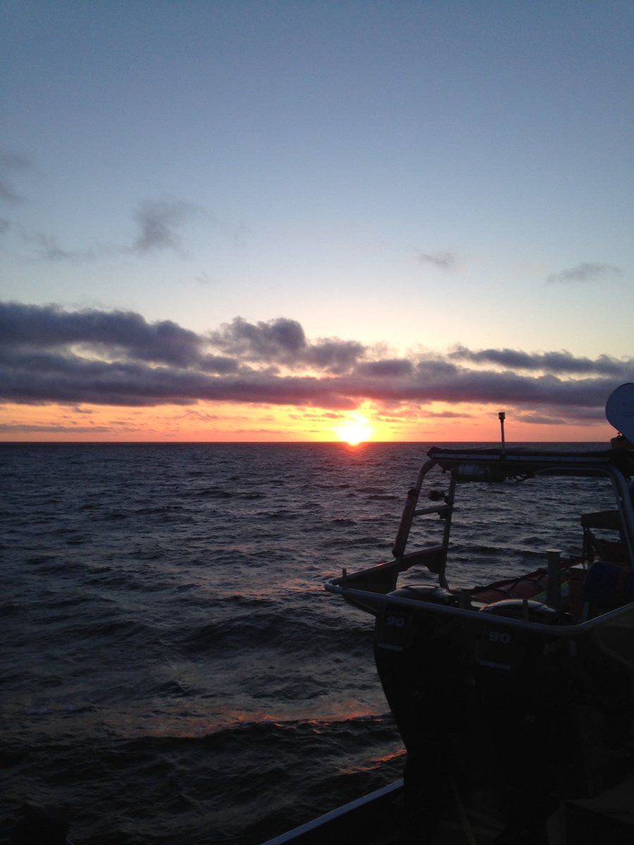 A sun rise over the ocean with a boat silhouette in the foreground.