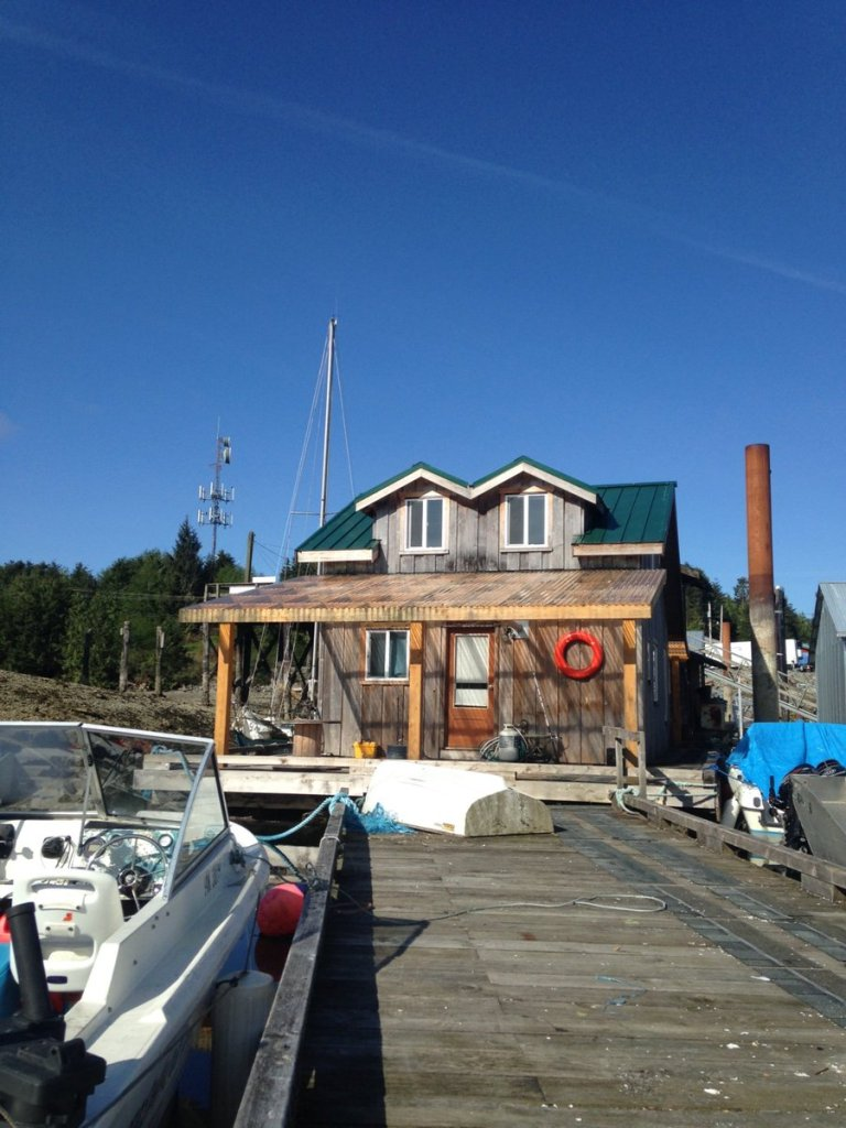 Looking up a dock with boats moored at the sides with a wood and green house at the end of the dock.