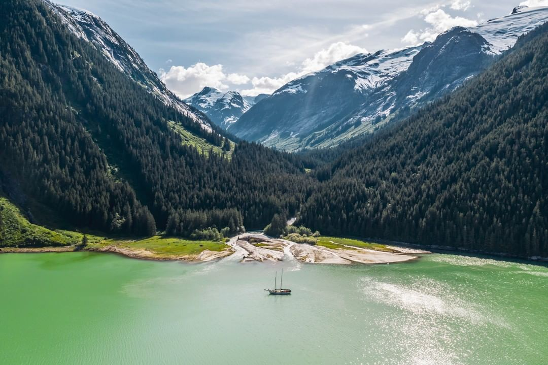 A sail boat on green-tinged water cradles between mountains covered with trees and snow.