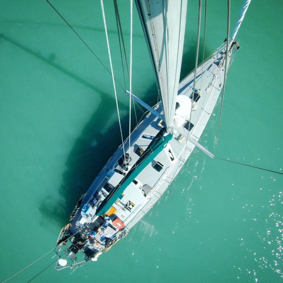 Aerial shot of the Achiever, Raincoast's research vessel, a white boat with white sails