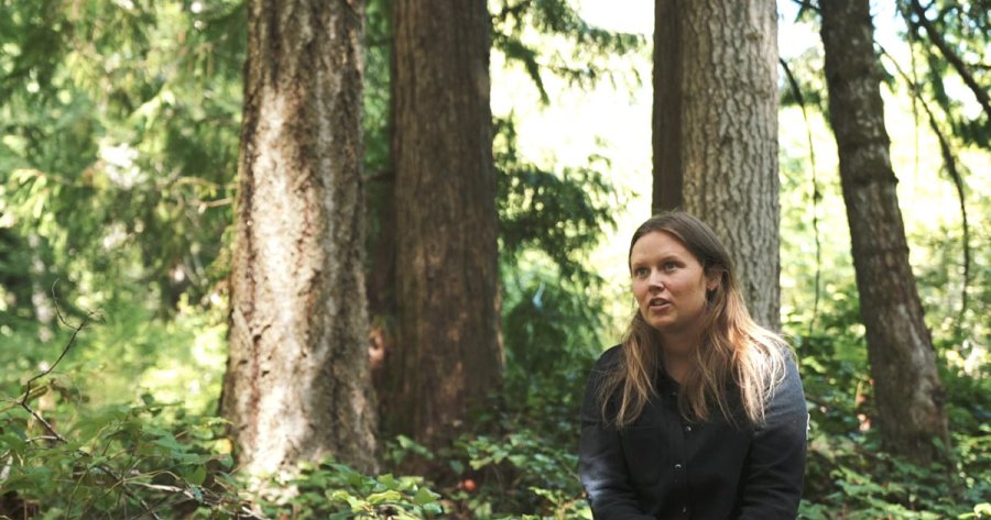 Megan Adams, biologist, sits in the forest to talk about her work in Wuikinuxv.