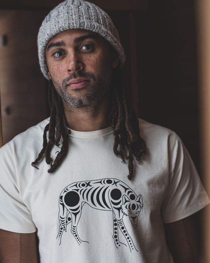 A man stands leaning on wooden wall wearing a grey toque and an off white Tee shirt that is part of the 1200 Wolf Tee shirt series by the company Ecologyst.