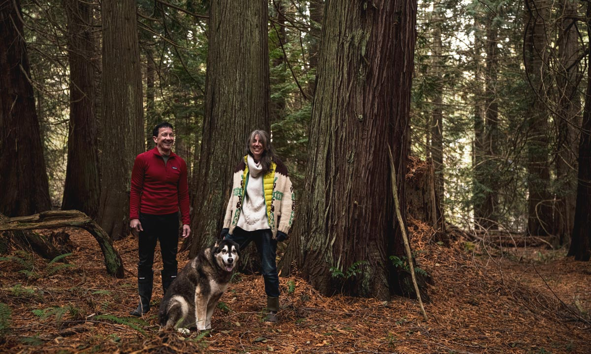 Chris Genovali and Misty MacDuffee and Atticus stand in the forest on Pender Island.