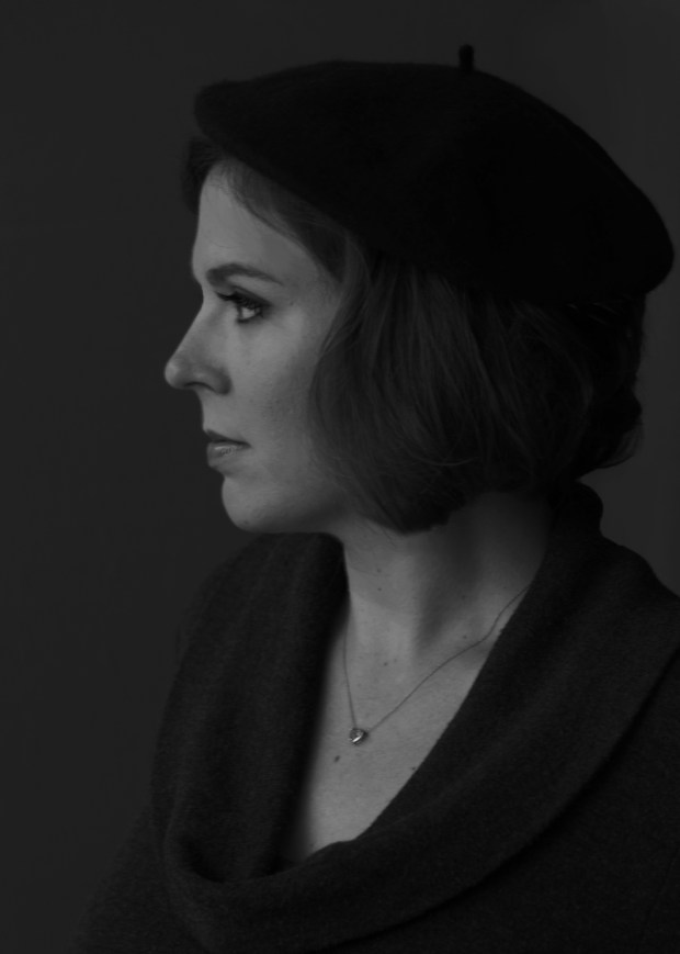 Thoughtful black and white portrait of woman showing her profile and wearing a beret.