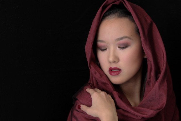 Young girl with shawl draped around her head in a tender moment.