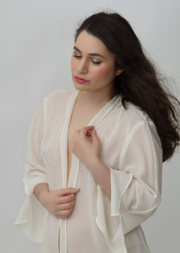 Intimate portrait of young woman in soft cream blouse with wind blowing her hair.