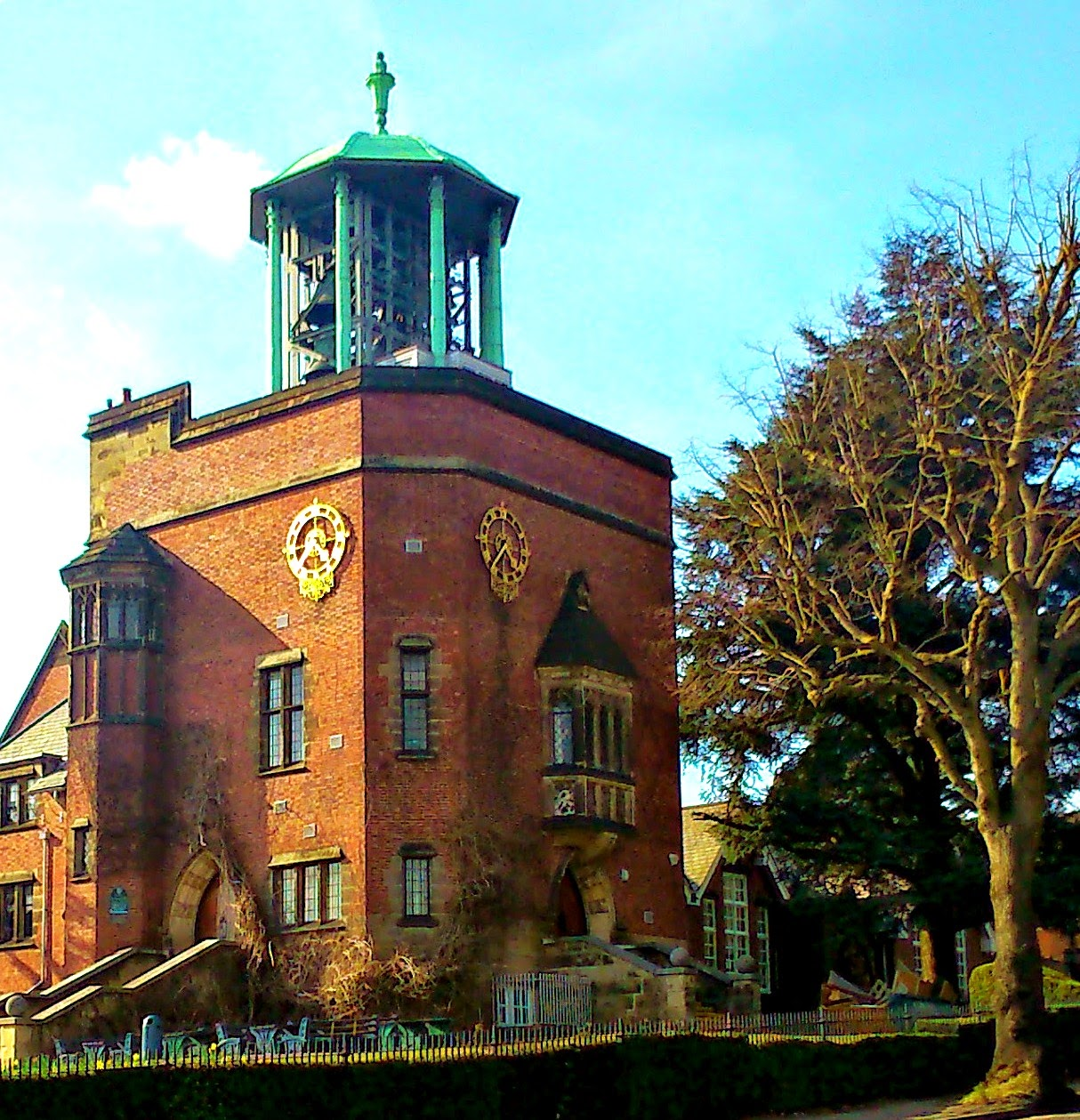 a large brick tower with a huge bell tower on the top, set against a pale blue sky