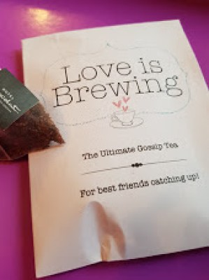 a teabag in a little bag with the words, love is brewing the ultimate gossip tea for best friends catching up