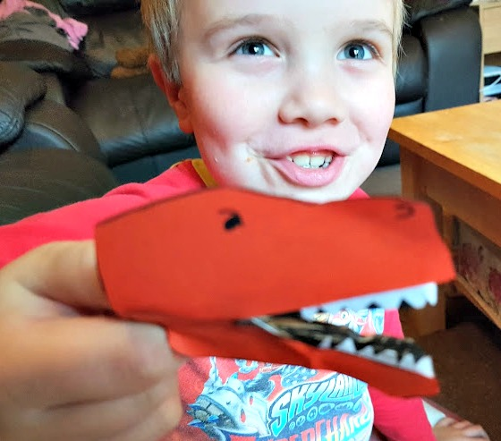 The Little Man holding his dinosaur peg head