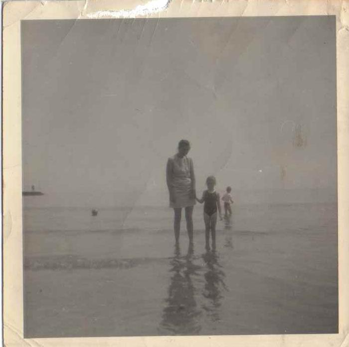 an old black and white photo of me and my mum paddling in the sea