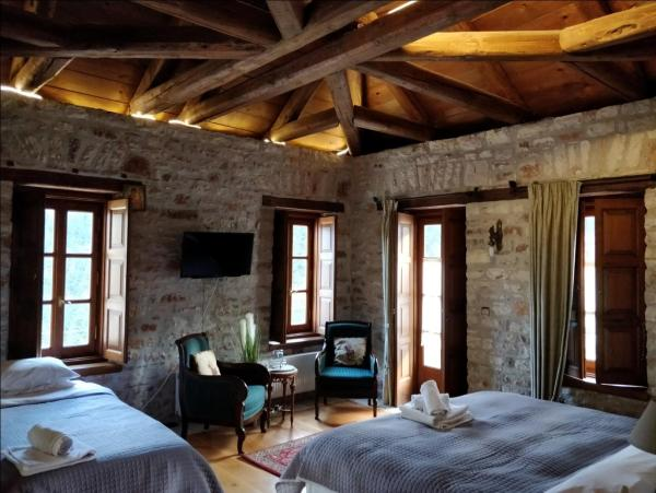a brick room with wooden ceiling and furnished with two beds