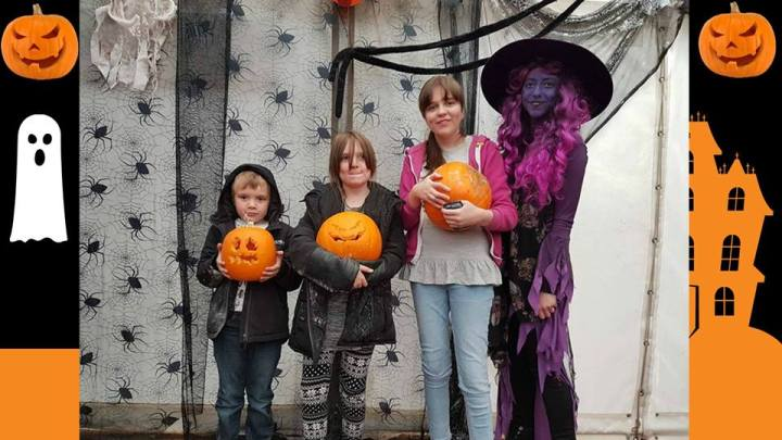 a line of my three children with their carved pumpkins with a purple witch.