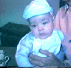 a grainy scanned photograph of a baby boy in a white hat and bib