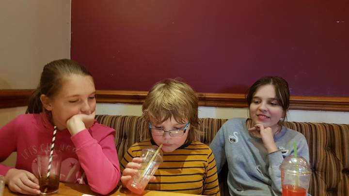 Three children sitting at the table at a restuarant
