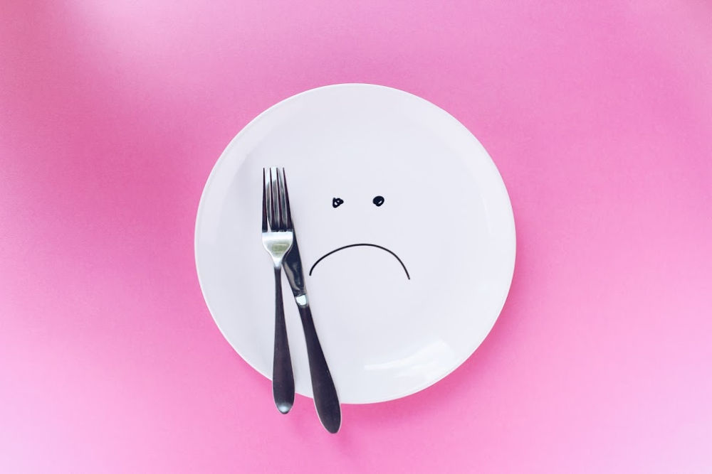 pink background with a white empty plate. On the plate is a sad face drawn with pen and a knife and fork