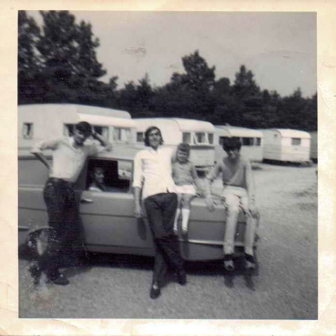 A Robin Reliant car in a caravan park. A man is behind the wheel and three young men standing by the car with a young girl sitting on the bonnet. The photo is black and white.