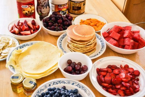 a photo of a selection of pancakes with lots of different topping choices