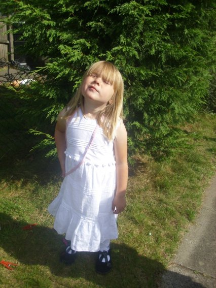 a very innocent looking little six year old in a white dress standing by a tree.