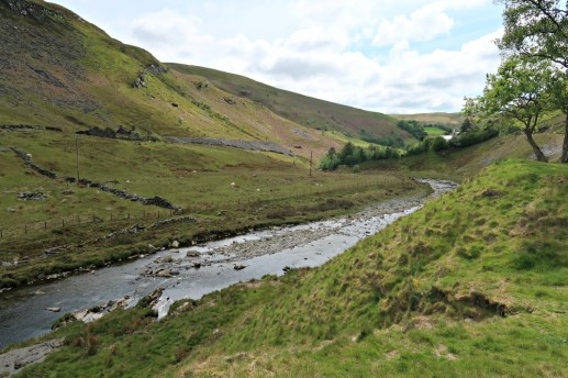 Elan Valley, big green hills with a river flowing through it.