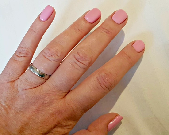 a hand with pink nail varnish