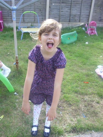 a little girl in the garden pulling a funny face, one of my facebook memories