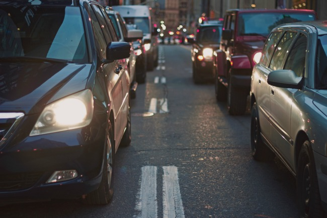 cars using their brakes in busy traffic in low light with headlamps on.