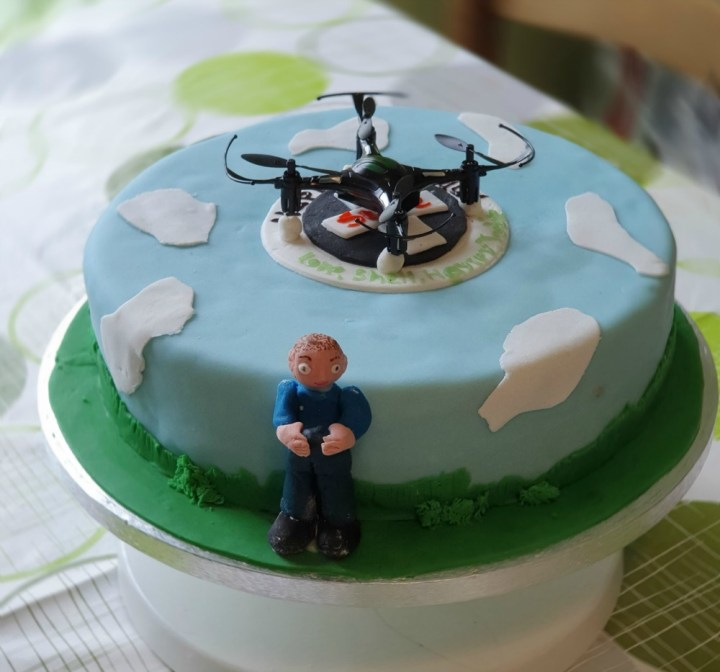 drone cake, a sky blue cake with clouds and an icing figure of a man standing at the side with a mini drone sitting on the top