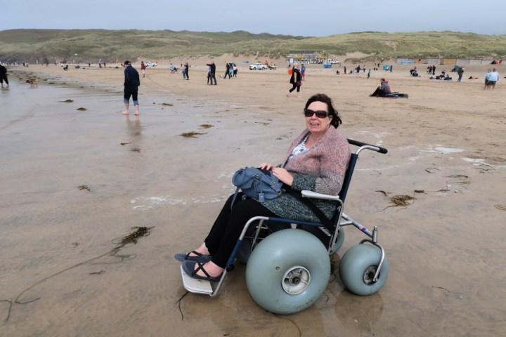 A Woman sitting in a beach wheelchair at the edge of the sea.