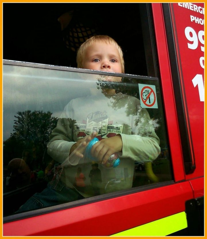 A little blonde haired boy looking out of the window of a fire engine