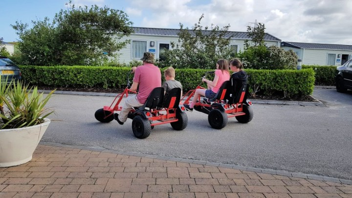 Two go karts from behind. One with a man and a young boy, the other with two young girls. They are in a caravan park.