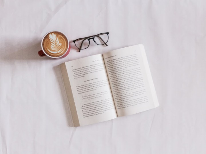 book open on white background with glasses and coffee