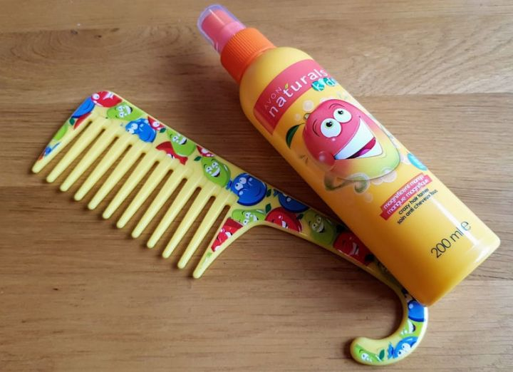 photograph of a colourful detangling comb and a bottle of detangling spray.