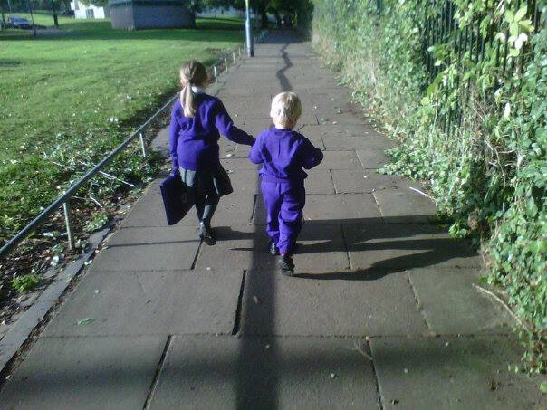 The backs of two young children in purple uniforms walking to school