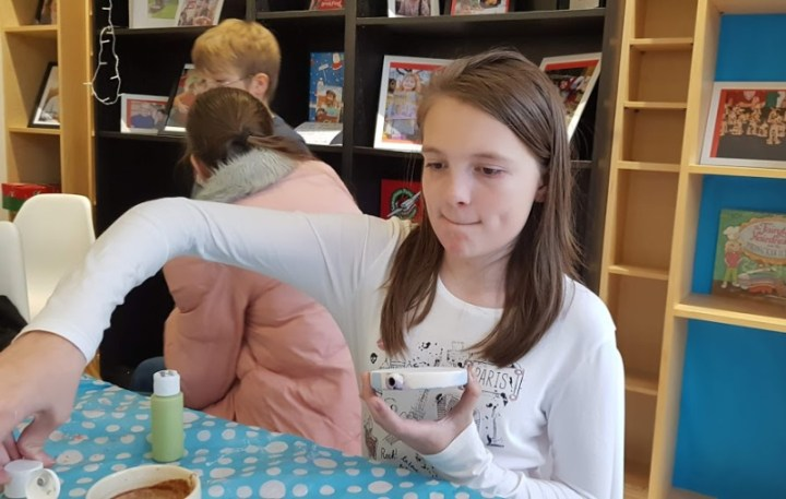 Boo concentrating (biting her lip) while painting a piece of Christmas pottery. Two other children chatter in the background by some bookshelves.