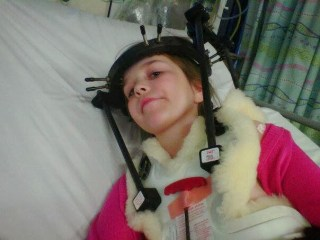 little girl in hospital bed with a halo brace